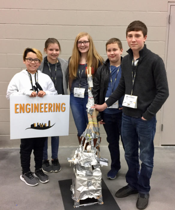 Engineering five-student team with sign and model