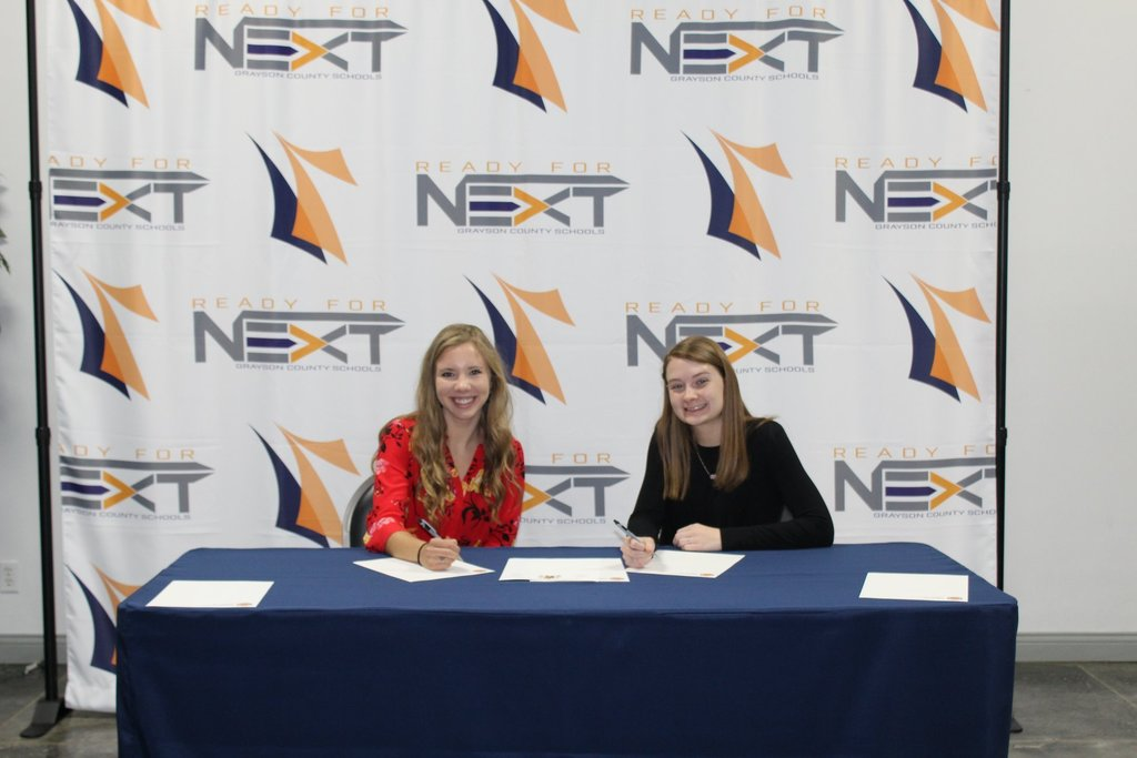 Two girls sign a paper at a table