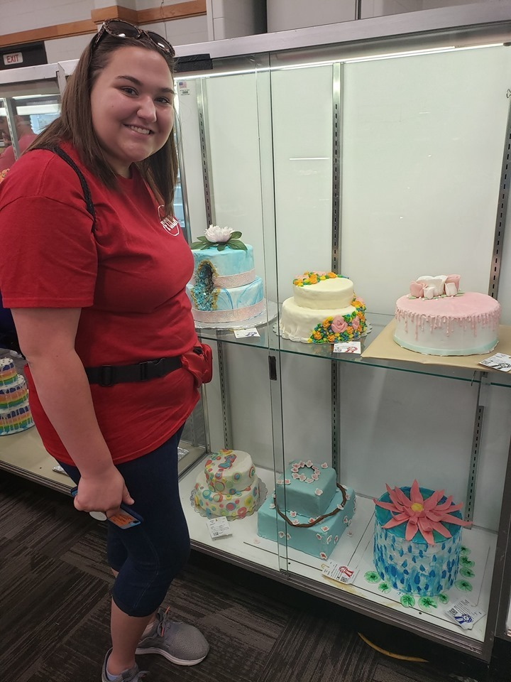 Girl standing in front of cake case