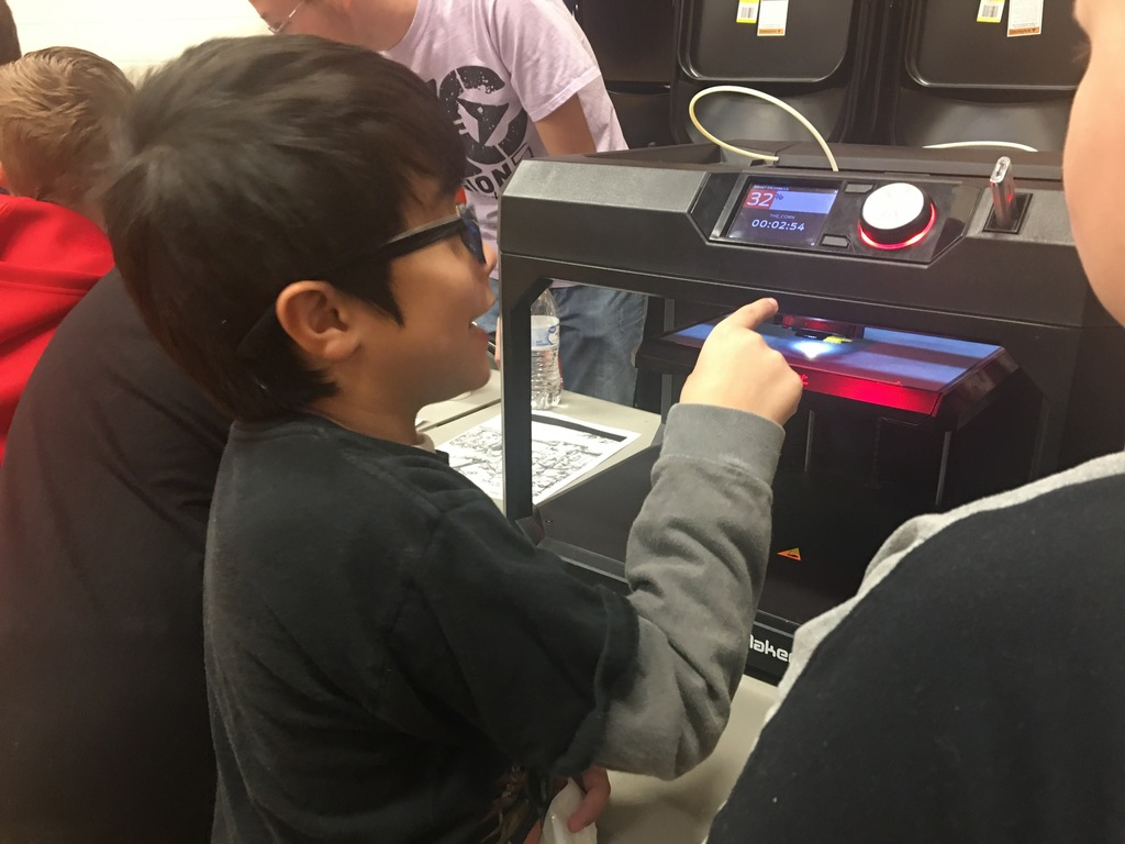 boy pointing to 3d printer