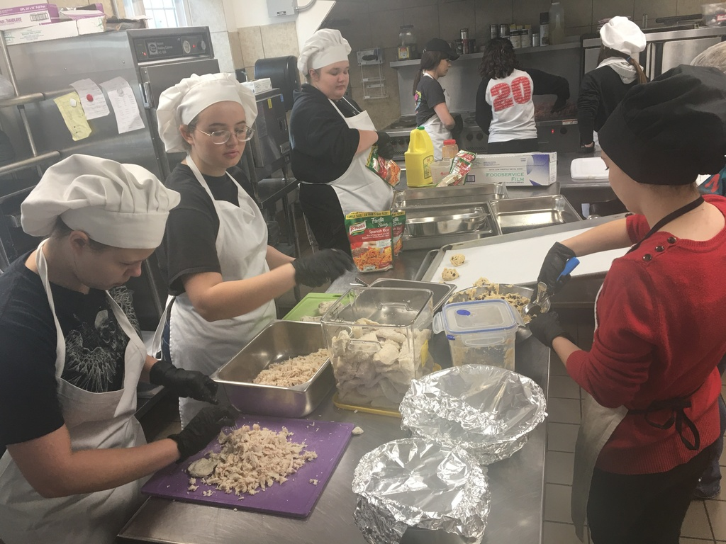 students prepare food in commercial kitchen