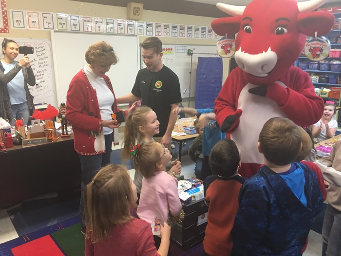 bel rep gives Jackie Pierce her basket while Laughing Cow entertains students