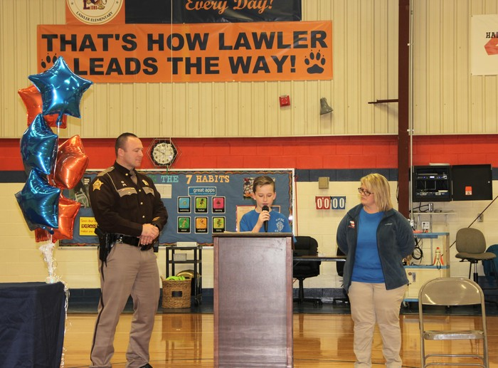 Sheriff and teacher watch boy speaking at podium