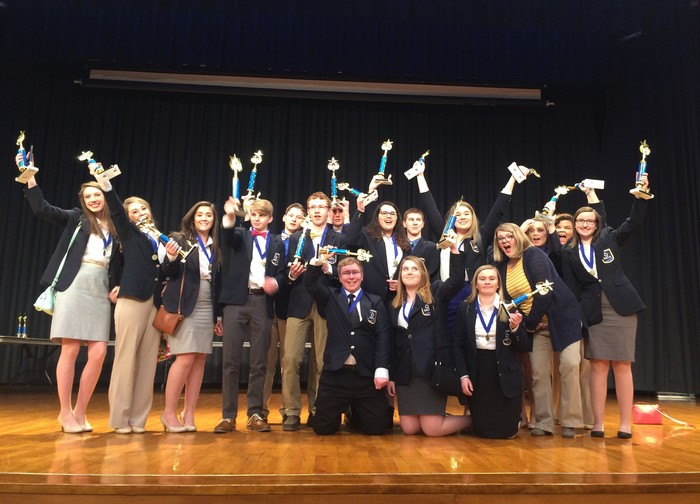 DECA Members celebrate with trophies on stage after Regionals wins