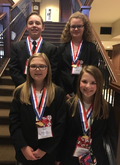 4 GCMS Jr. HOSA 1st place winners on stairs wearing medals