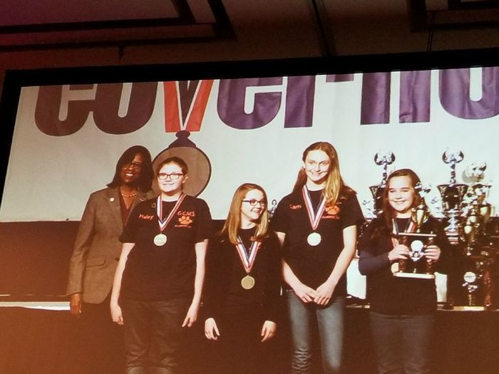 GCMS FPS team on stage with trophy and wearing medals