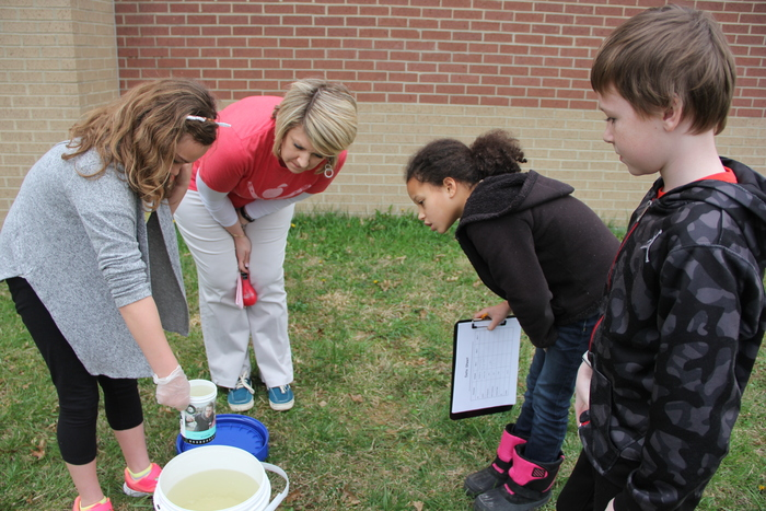 Students and teacher watch as girl dips water form a bucket