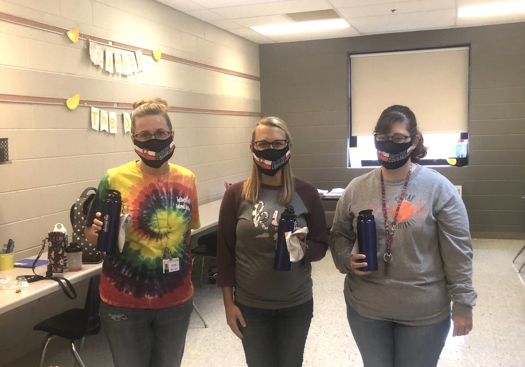 threes women in masks with water bottle